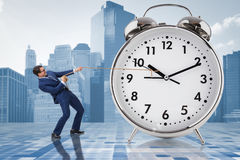 The businessman pulling clock in time management concept. Businessman pulling clock in time management concept Royalty Free Stock Image