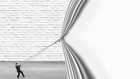 Businessman pulling down blank white curtain covering brick wall. Businessman pulling down blank white curtain covering white brick wall and gray concrete floor royalty free stock photo