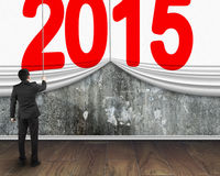Businessman pulling down 2015 curtain to cover mottled concrete Stock Photo