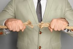 Businessman pulling frayed rope in opposite directions. On gray background royalty free stock photos