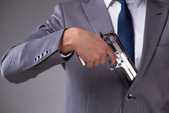 The businessman pulling the gun out of pocket Stock Photography