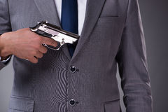The businessman pulling the gun out of pocket Stock Image