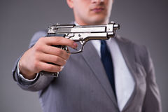 The businessman pulling the gun out of pocket Stock Photo