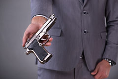 The businessman pulling the gun out of pocket Royalty Free Stock Photo
