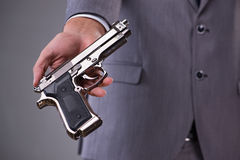 The businessman pulling the gun out of pocket Royalty Free Stock Images