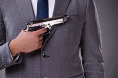 The businessman pulling the gun out of pocket Royalty Free Stock Photos