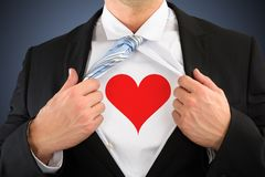 Businessman pulling his shirt showing heart shape symbol Stock Photo