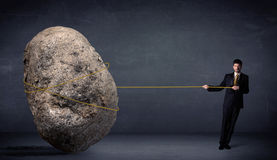 Businessman pulling huge rock with a rope. Concept on background Royalty Free Stock Photography