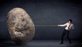 Businessman pulling huge rock with a rope Royalty Free Stock Images