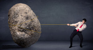 Businessman pulling huge rock with a rope Stock Photography
