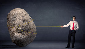 Businessman pulling huge rock with a rope Stock Photos