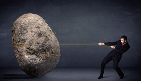 Businessman pulling huge rock with a rope Royalty Free Stock Image