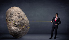 Businessman pulling huge rock with a rope Royalty Free Stock Photo