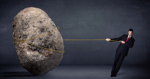 Businessman pulling huge rock with a rope stock images