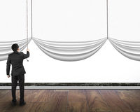 Businessman pulling open blank curtain with empty white backgrou Royalty Free Stock Image