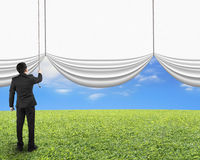 Businessman pulling open blank white curtain revealed natural sk Stock Photos