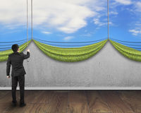 Businessman pulling open natural sky curtain covered concrete wa Stock Images
