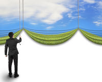 Businessman pulling open natural sky meadow curtain revealed bla Stock Photo