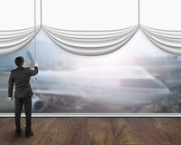 A businessman pulling open white blank curtain showing airplane Royalty Free Stock Image