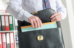 Businessman pulling out folders from his briefcase Royalty Free Stock Images