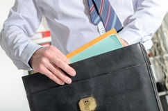 Businessman pulling out folders from his briefcase Stock Images
