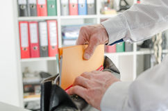 Businessman pulling out folders from his briefcase Royalty Free Stock Image