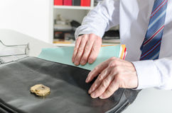 Businessman pulling out folders from his briefcase Stock Image