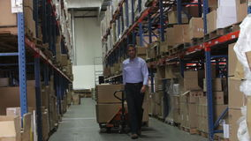 Businessman Pulling Pallet In Warehouse stock video footage