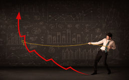 Businessman pulling a red arrow upright with a rope Royalty Free Stock Image