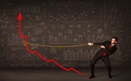 Businessman pulling a red arrow upright with a rope Royalty Free Stock Images