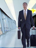 Businessman pulling rolling luggage in airport concourse Stock Photo