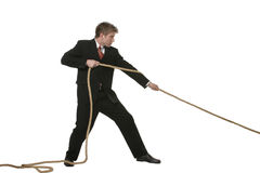 Businessman Pulling on Rope. Concept of businessman pulling on rope stock photo