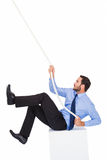 Businessman pulling a rope with effort. On white background Royalty Free Stock Photo