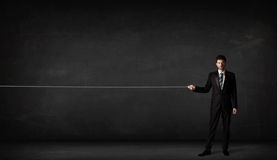 Businessman pulling rope on grey background Royalty Free Stock Images