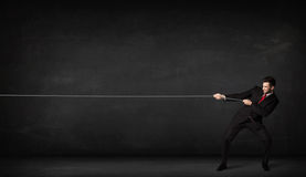 Businessman pulling rope on grey background Stock Images