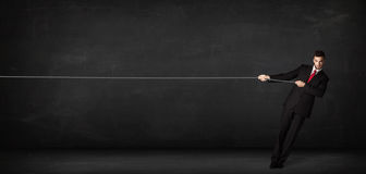 Businessman pulling rope on grey background Royalty Free Stock Image