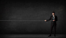 Businessman pulling rope on grey background. Concept Stock Images