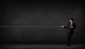 Businessman pulling rope on grey background Royalty Free Stock Photography