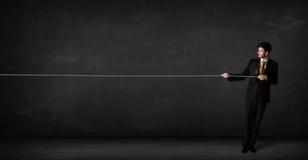 Businessman pulling rope on grey background Stock Photos