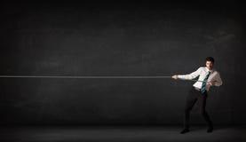 Businessman pulling rope on grey background Royalty Free Stock Photo