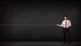 Businessman pulling rope on grey background Royalty Free Stock Image