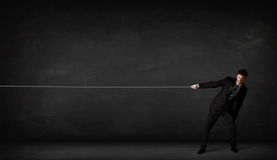 Businessman pulling rope on grey background. Concept Royalty Free Stock Image