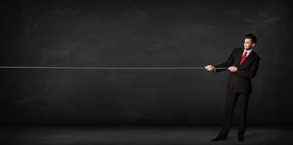 Businessman pulling rope on grey background. Concept Stock Photo