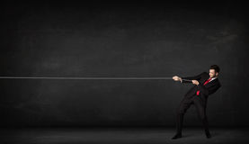Businessman pulling rope on grey background. Concept Stock Photos