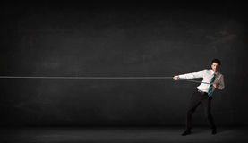 Businessman pulling rope on grey background. Concept Royalty Free Stock Photo