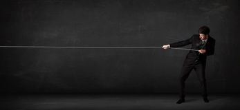 Businessman pulling rope on grey background. Concept Royalty Free Stock Photography