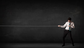 Businessman pulling rope on grey background. Concept Stock Image