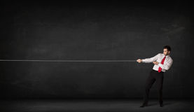 Businessman pulling rope on grey background. Concept Stock Photography