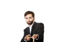 Businessman pulling a rope. Young handsome businessman pulling a rope Royalty Free Stock Images