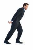 Businessman pulling something behind him Royalty Free Stock Image